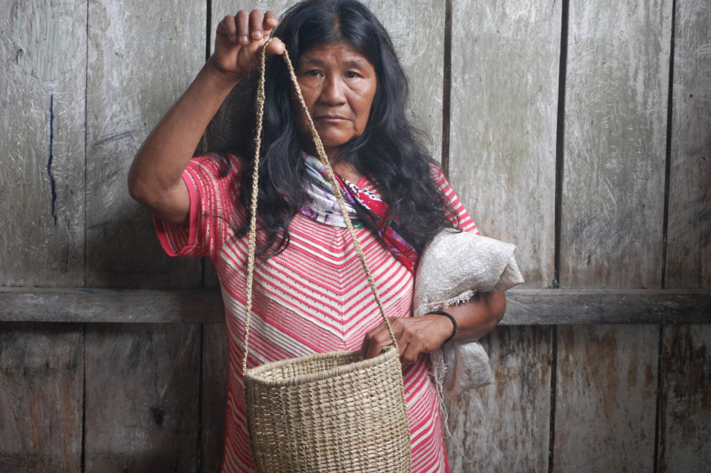 Artesã e seu cesto feito de cipó titica e fibra de tucum.