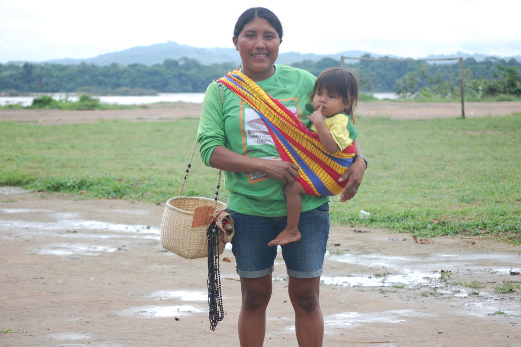 Artesã Parakanã com tipoia, cesto e colares feitos por ela.