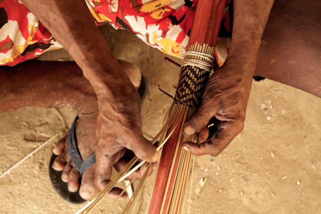 Guerreiro Kayapó confeccionando manualmente a borduna, artefato tradicional feito pelos homens da aldeia. (Foto: Simone Giovine/AFP)